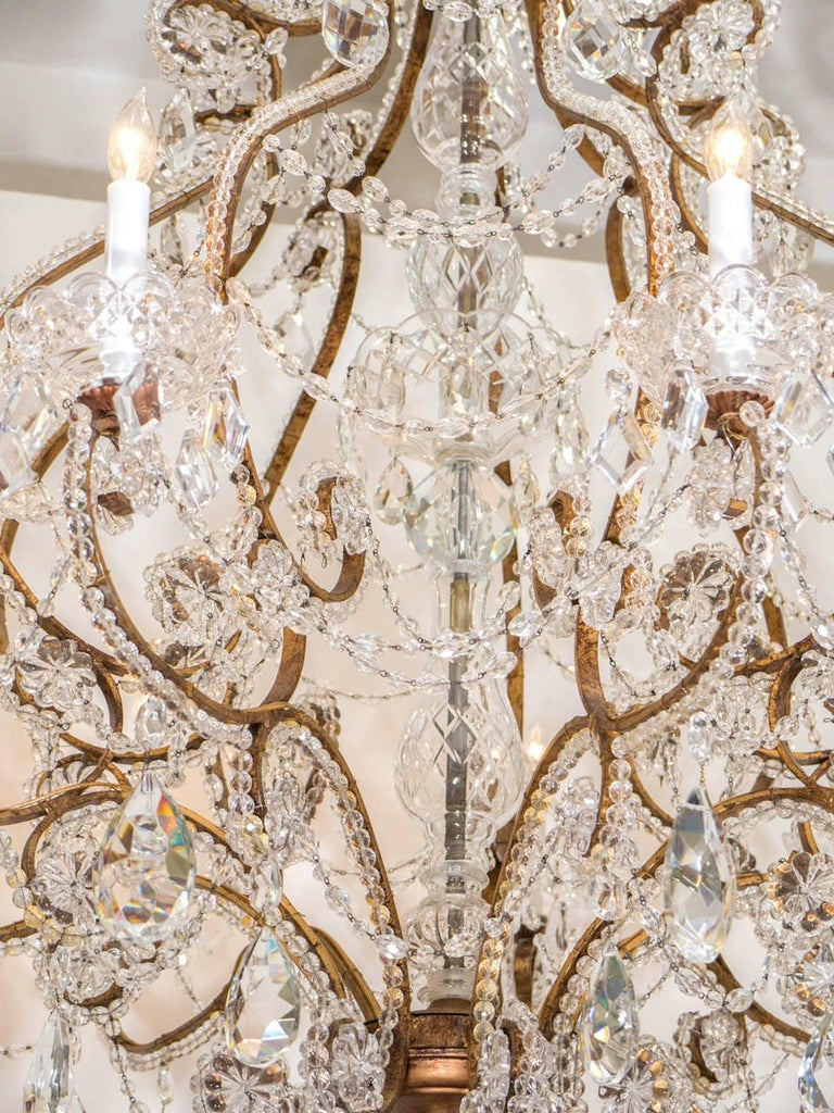 Majestic and fanciful gilt iron framed chandelier adorned with strands of faceted crystal beads and drops. Chandelier has nine-light sources surrounded by an etched crystal bobeches and have been rewired for use in the USA. A stunning addition to