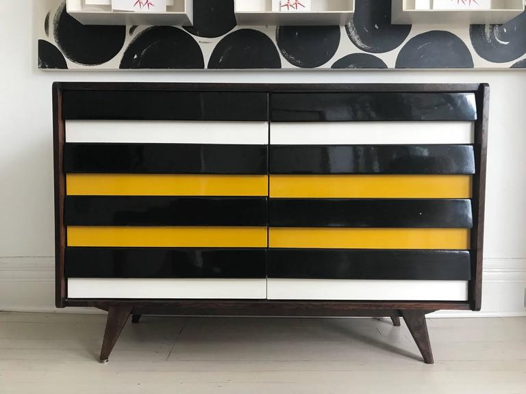 Walnut chest of drawers designed by Jiri Jiroutek for Interier Praha. High gloss black, white and yellow wood drawers four on each side.