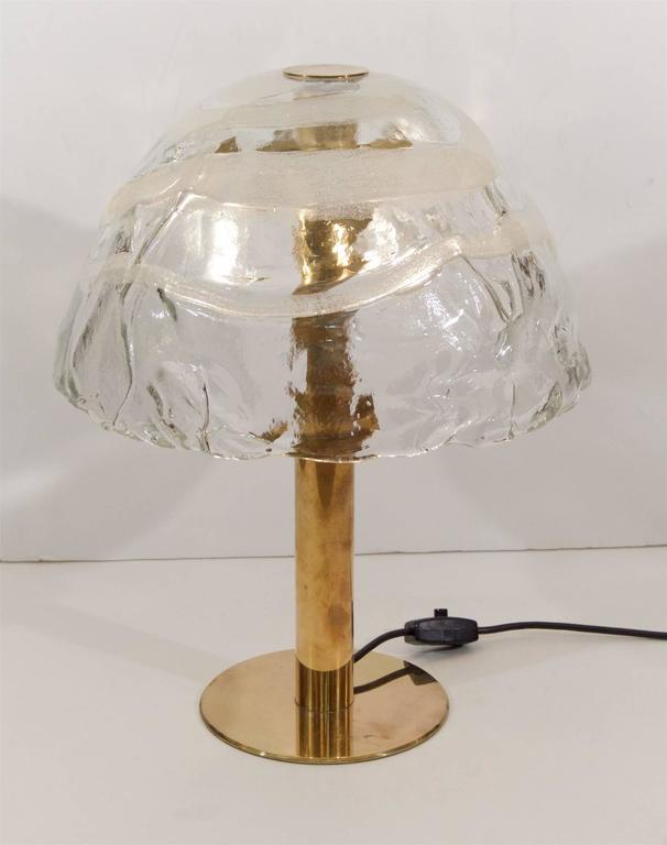 An incredibly unique brass table lamp by Kalmar with a fused glass shade. The glass shade features dramatic texture and fused glass in swirls of white.  Original wiring verified functioning, with a new American plug. Takes three medium base bulbs