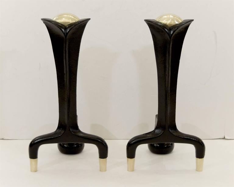 Elegantly formed black enameled iron andirons and high polish brass accents by Donald Deskey.