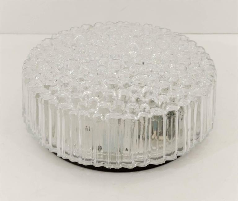 A beautiful glass flush mount with a raised etched glass bubble pattern with singular cuts on the side to create a linear pattern.  Takes one medium base bulb up to 60 watts, new wiring.