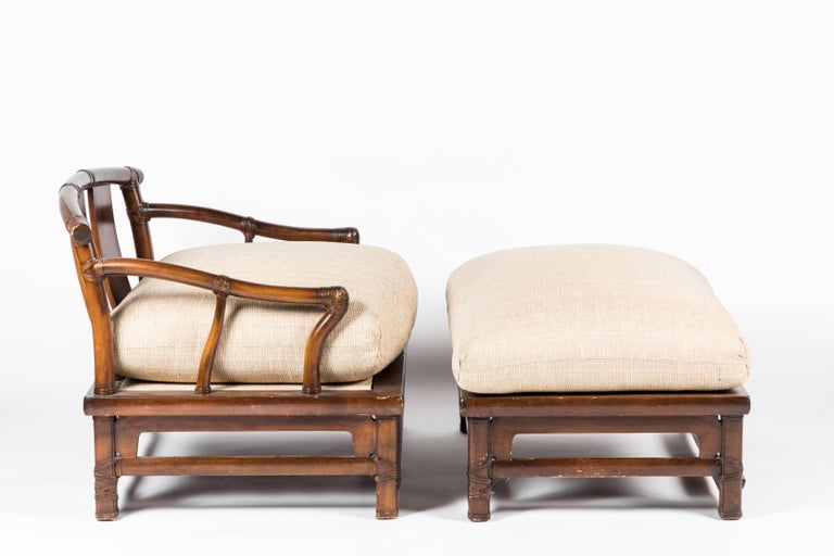 Oversized yoke-back Asian style armchair with matching ottoman by Henredon from the 1990s. Executed in pecan wood with upholstered cushions.