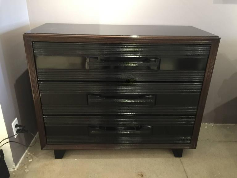 Three large drawers (top one with removable dividers) with Art Deco streamlined design and finished with piano quality lacquer black with deep mahogany brown trim. These are a pair.