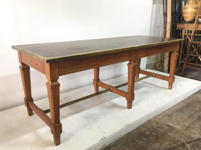 Equipped with two front drawers, original key (single key locks both drawers) and brass molding which frames the top in aged cognac leather. Brass stretcher at base. Exceptional design very much after Jacques Adnet. This piece is great scale as a