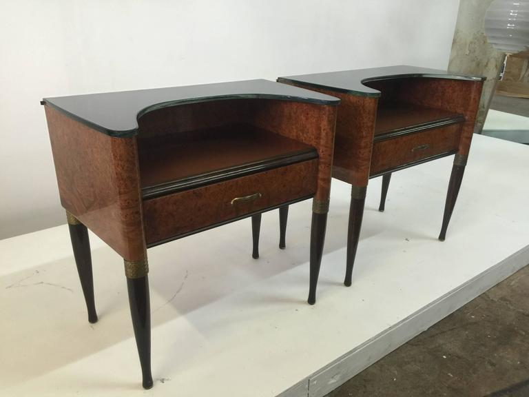These are rare! A wonderful pair of two-tiered night tables. Single drawer each with original brass hardware and accents. Glass is all original on both levels, top shelf level is a curved glass for added flair! Burl wood and walnut.