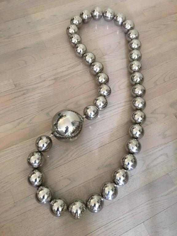 This wonderfully large department store display piece necklace is made of mirror finish stainless steel orbs strung together. As shown it hangs 4 feet.