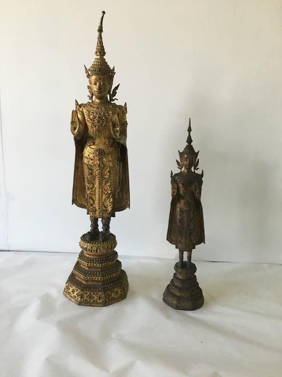 Late 19th century - beautifully preserved coloring.  Dimensions of taller: 33 inches tall (price $4,600).  Dimensions smaller: 22.5 inches tall (price $3,300).  This Buddha in standing position was executed in a typical Laotian style, which