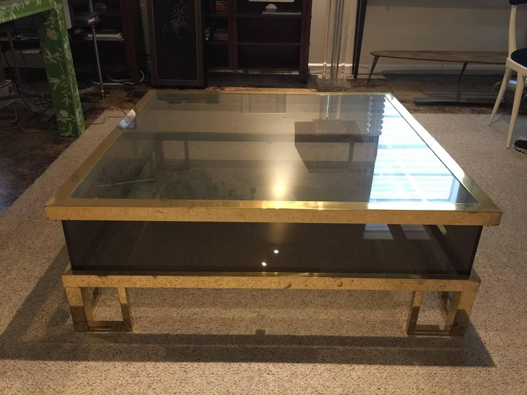Sliding top to reveal a large vitrine area for display. Brass frame with squared legs and smoked glass.