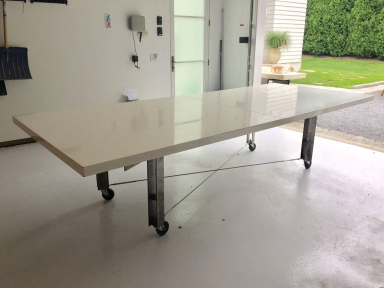 Amazing Industrial steel dining or work table; The table frame is of very high and heavy quality by renowned Architect, James D'Auria. Wheels lock to keep it in place, steel cable stretchers and lacquered top in two large sections.  James D'Auria