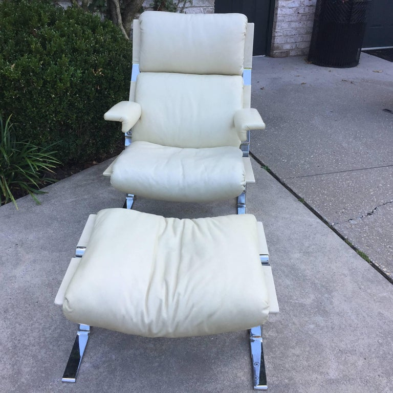 Original ivory leather on this vintage Saporiti lounger and ottoman. Very heavy steel framed and comfortable lounge chair with matching ottoman is made in Switzerland by Saporiti. Ottoman dimensions are: 26 inches wide, 18.5 inches deep, 17 inches