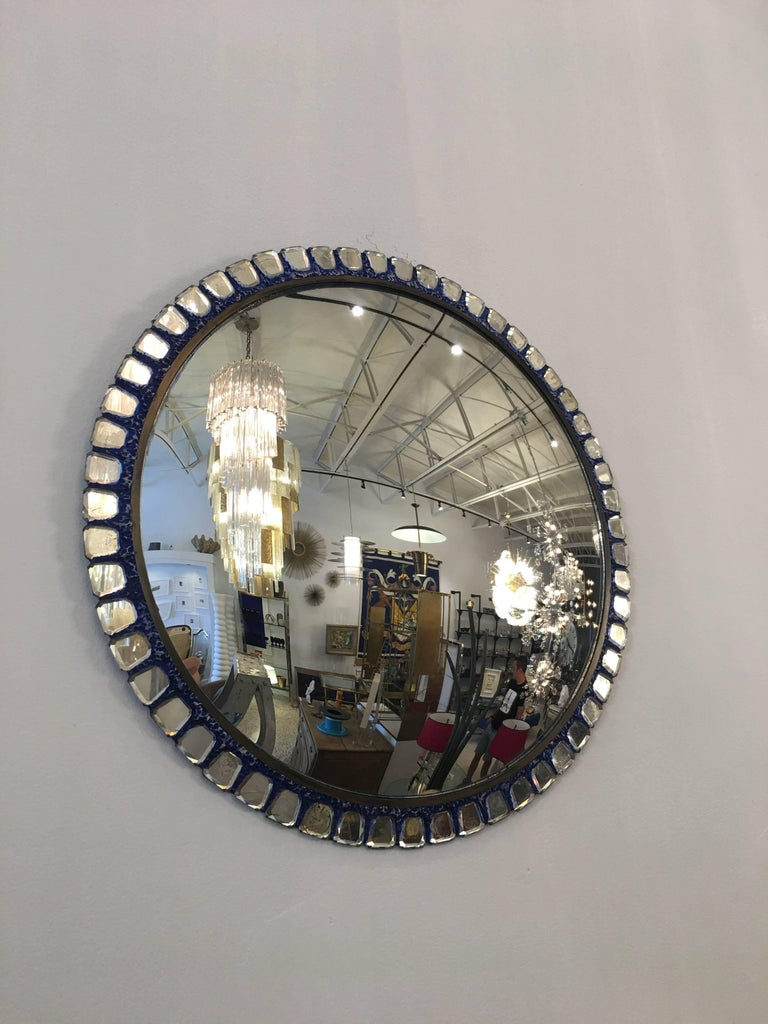 Exquisite details throughout small faceted mirrors surround this convex wall-mounted mirror. A subtle Yves Klein blue tint to plaster mold surround. Brass trim surround makes this a solid and important Vautrine style treasure.