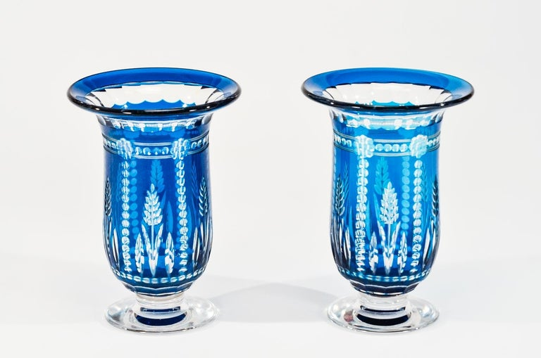 This pair of Val Saint Lambert handblown vases are tall, dramatic and solid. The unusual teal blue/marine blue overlay is cut to clear with clean lines in a true Art Deco motif, designed by one of the master artists, Joseph Simon. Head of the design