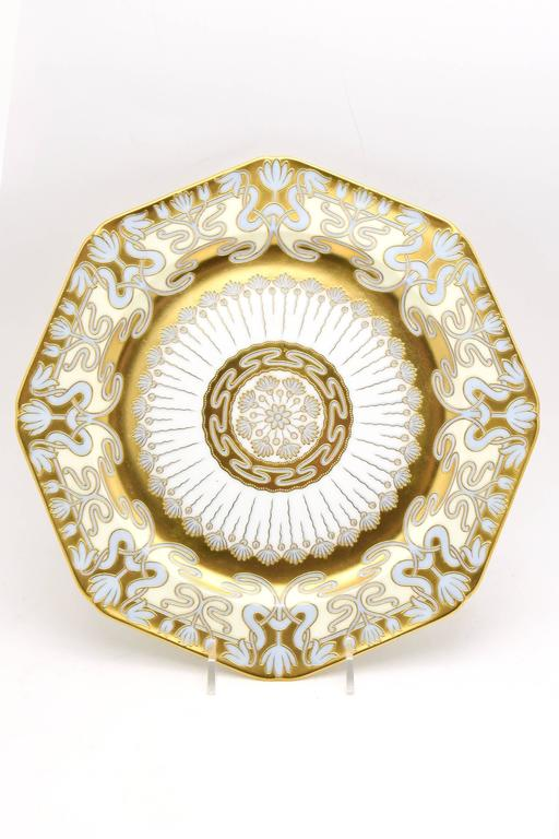 This is a very rare set of 12 Cauldon service/presentation plates showcasing Art Nouveau decoration at it's finest. Hand-painted raised paste gold over robin's egg blue creates a soft and elegant contrast to the flowing lines of the gold decoration.