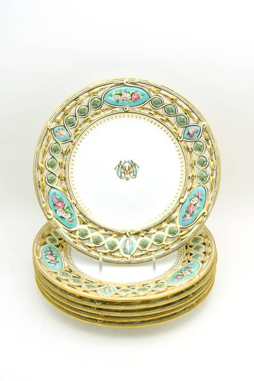 This unusual dessert service consists of six plates and two matching footed compotes with amazingly intricate pierced borders. Each piece is uniquely hand painted with flowers and shells and embellished in gold. The reserves are painted with a soft