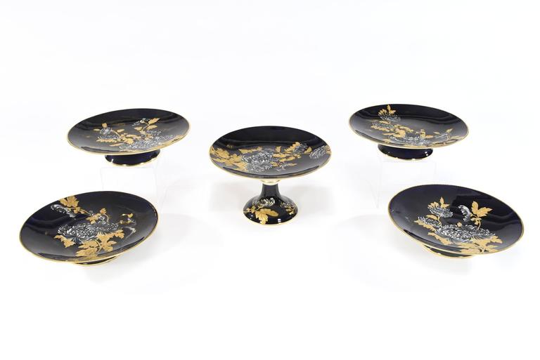 Made by the renown English porcelain firm of Davenport, this set of ten dessert plates and five serving pieces are all hand painted with a variety of chrysanthemums and foliage. What sets this apart is the fantastic contrast of raised paste gold and