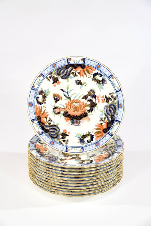 The polychrome enamel Japonesque motif, using the Imari palette decorates these 12 pristine dessert plates made by Royal Crown Derby. The combination of soft blue, cobalt blue, bittersweet orange and green all trimmed and highlighted in gold makes