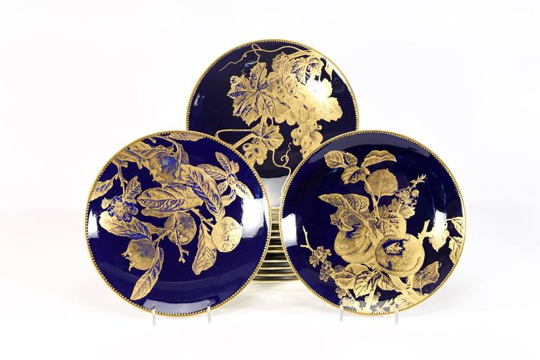 This set of 12 Brownfield 19th century dessert plates exemplify the Aesthetic Movement at its finest. Each plate is uniquely decorated with a gold overlay depicting different fruit specimens, including insects and foliage, all placed off center in