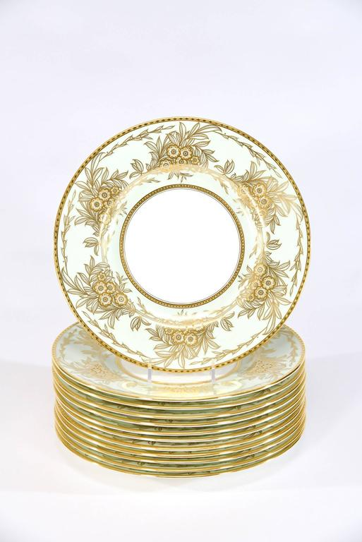 """This set of 13 Minton dinner plates feature the iconic """"Eau de Nils"""" enamel border which is a soft blue green, described as the """"water of the Nile"""". The clean white centres are framed with a lovely raised paste gold floral Arts"""