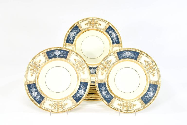 This set of 12 Minton dinner plates exhibits the beauty and quality of Minton's top of the line offerings. The acid etched gold border frames the three neoclassical reserves of raised paste gold and beading alternating with three blue reserves