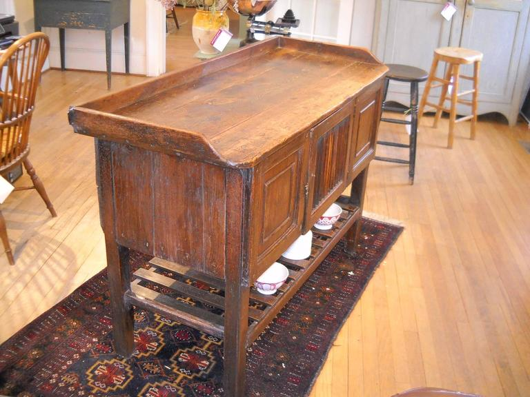 This is a total knockout. This piece could be used against a wall or as a freestanding island. A very rich golden brown patina adorns this one of a kind piece, complete with a slatted door that has storage inside the entire length of this piece and