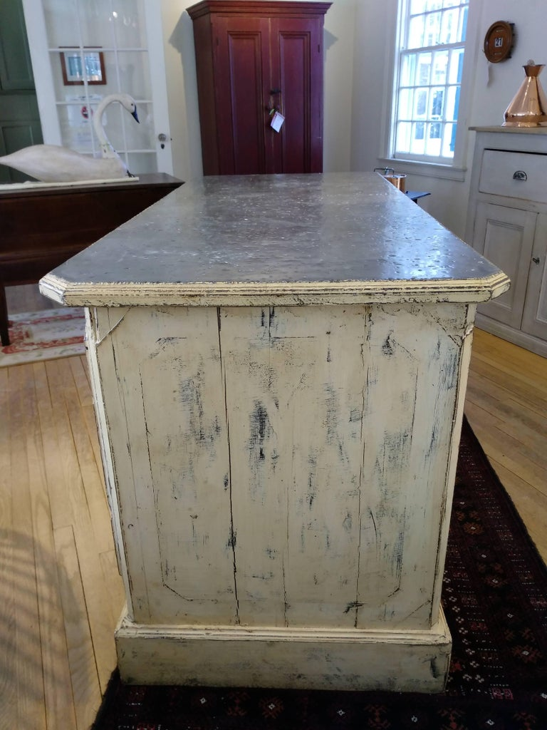 This piece came from a bakery store in the south of France. The piece is totally original, including the zinc top, hardware and shelves. It has been repainted by our dealer, a soft butter color. The counter is finished on all sides and has a door