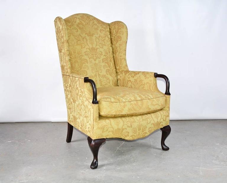 The vintage wingback armchair has wood extensions to the arms and cabriole legs, and is newly upholstered in a gold damask linen fabric. Easily comfortable.