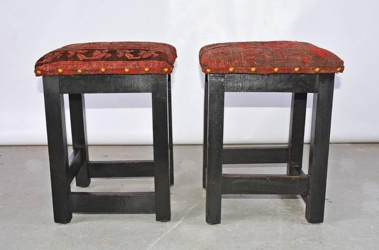 The pair of contemporary stools newly upholstered with remnants of antique mid-eastern carpet. The wood legs are painted black.