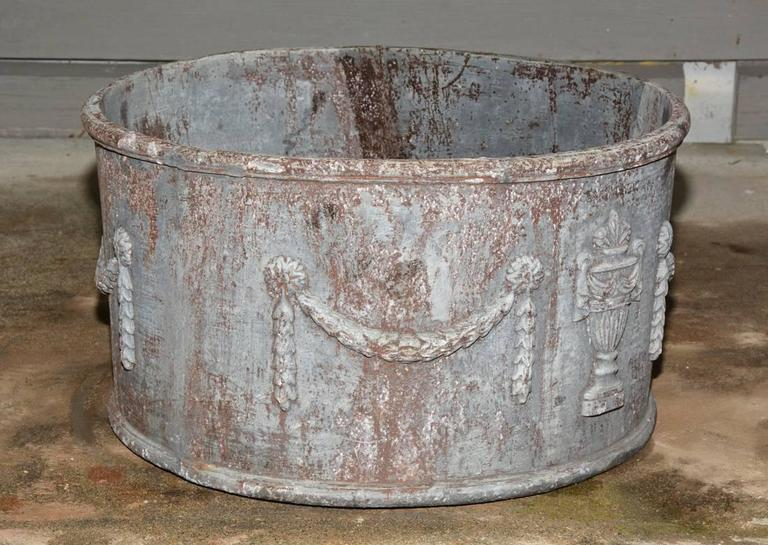 The classical style antique lead planter has a drainage hole and is decorated with swags and urns.