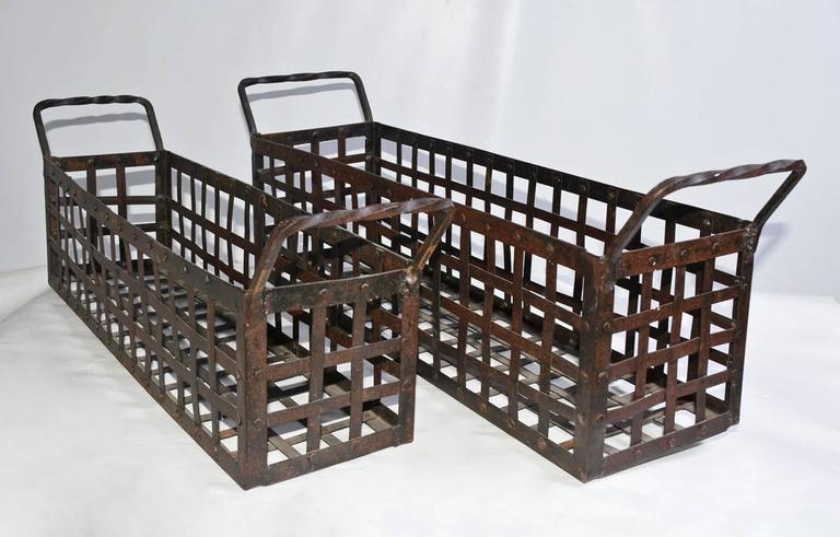 The pair of vintage wrought iron shell-fish baskets can be used as planters. The handles are twisted and the strapping is interwoven. One basket is smaller than the other.