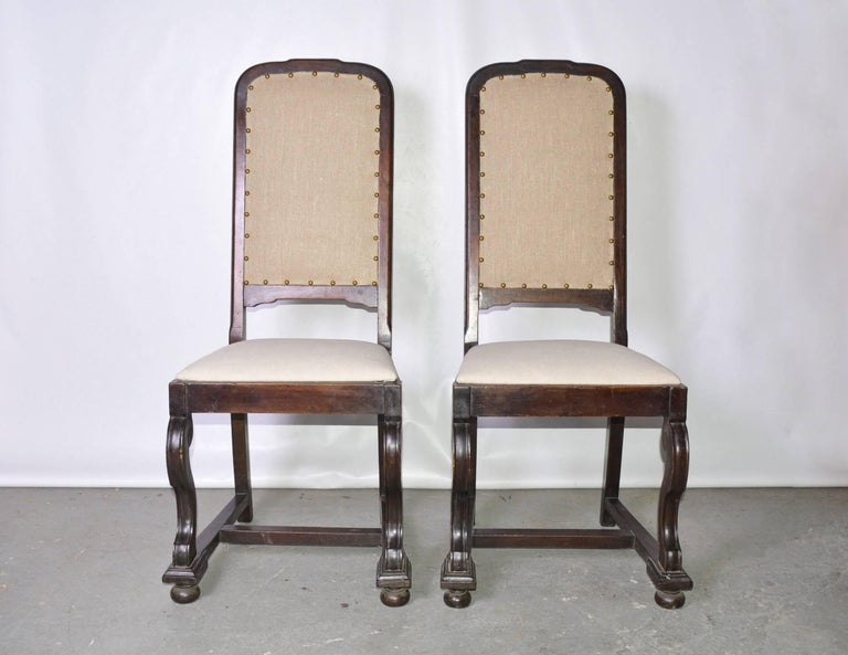The pair of antique Jacobean-style side mahogany chairs are newly upholstered in one shade of beige linen while the seats are covered in another complementary shade of beige linen.