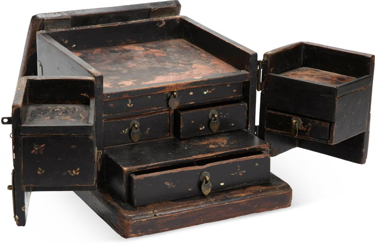 Black lacquered Chinese jewelry chest features two doors with brass mountings. The top lifts and folds away revealing drawers for storage. Wonderful aged patina.