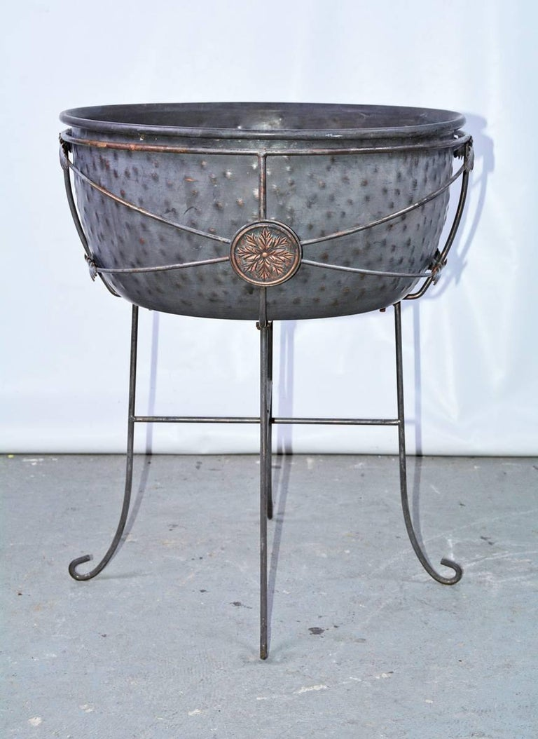 Iron planter or jardinières on stand with four c scroll feet and leaf shaped metal detail with leaf style medallion detail. Measures: approximate 25 inches tall 18 inches diameter.