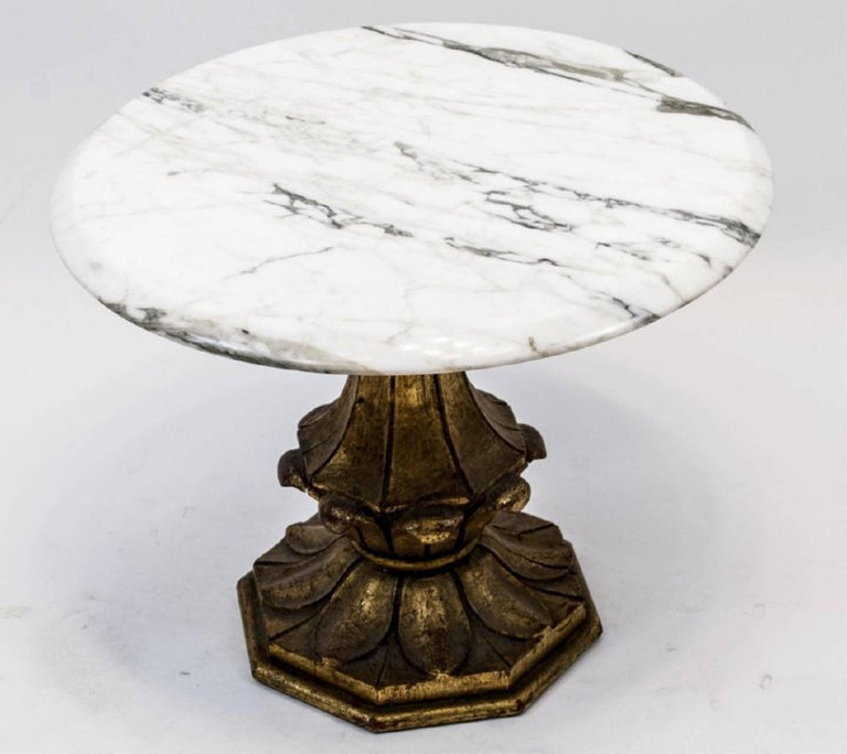 Marble side or occasional table features a round marble top and a hand-carved wooden base painted gold.