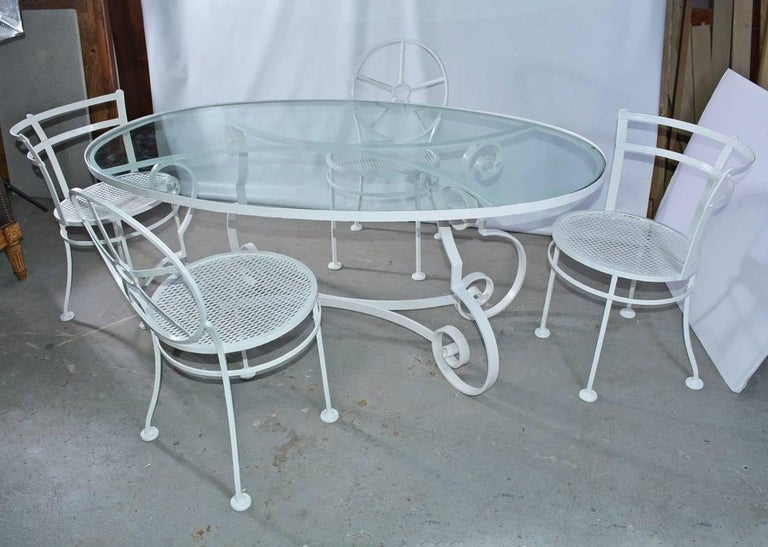 Indoor or outdoor oval metal and glass midcentury Patio/Porch garden table and four dining chairs. Dining table has an iron base and glass top. The base is designed with Baroque scroll legs and curved braces that match the curved braces supporting