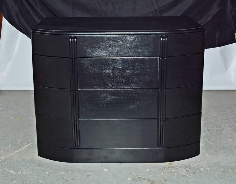 Painted glossy black, the moderne chest of drawers has a three-sectioned drawer at the top and three deep drawers below. The side boards of each drawer are set in the grooved curved front panels while the back edges of the side boards are dovetailed