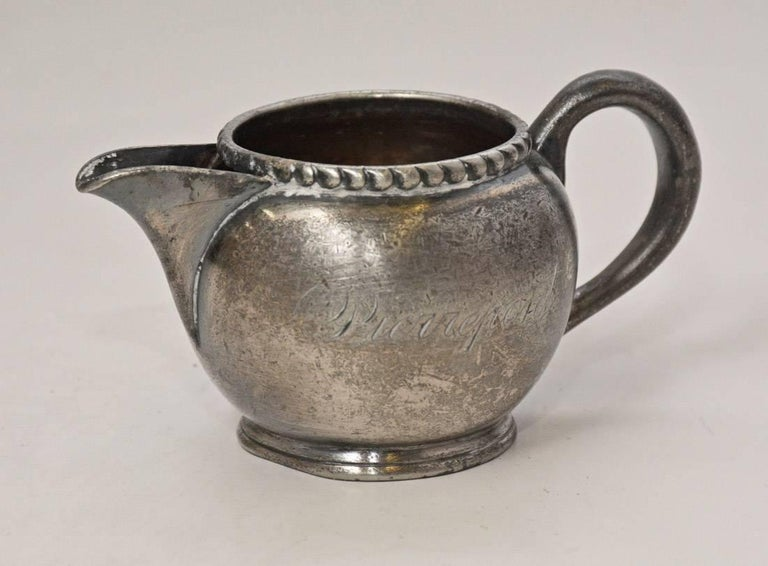 The small vintage pewter creamer has a beaded rim and is stamped on the side Pierrepont and on the bottom made and guaranteed by Meriden Company USA, 908 1/4 pt.