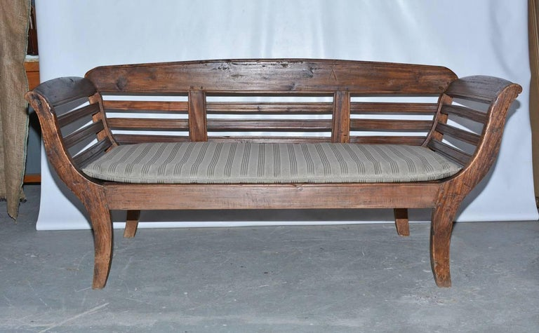 The antique teakwood bench sofa is solidly built and comes with slatted back and arms. The custom-fitted cushion is in a grey shadow stripe fabric.