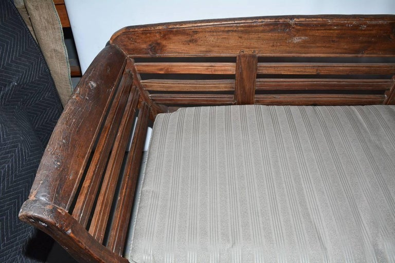 20th Century Antique Teak Settee with Slatted Back, Arms and Cushion For Sale