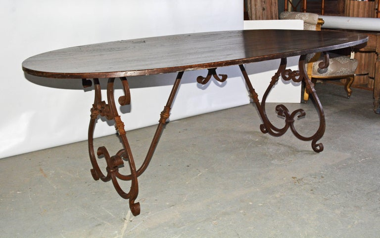 Elegant and rustic at the same time, the French Baroque style hand-forged iron trestle base features two lyre-shaped legs adorned with a weathered rust finish, connected to the underside of the top with a curved stretcher. The delicate volutes,