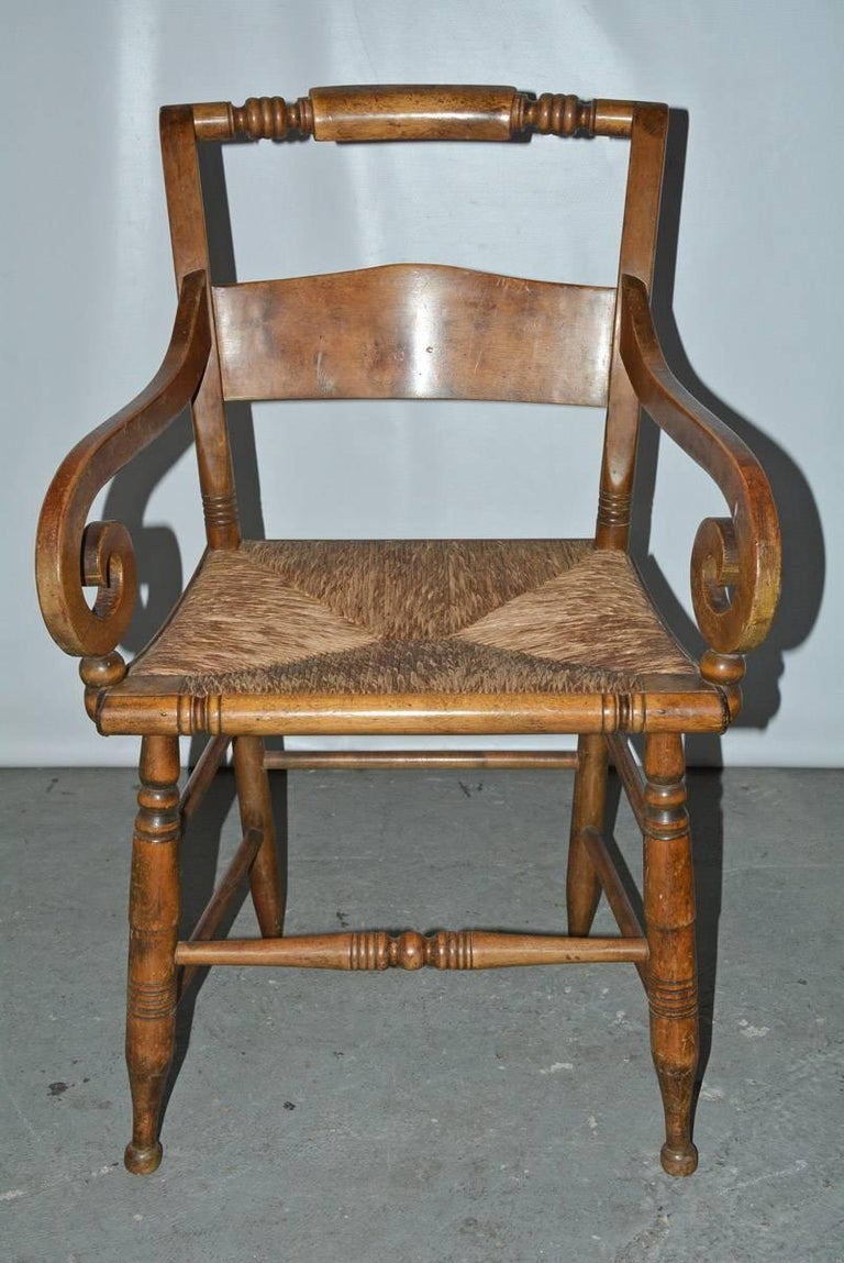 The wood country dining or desk chair with a woven raffia seat is in the style of early 19th century American Empire with turned back and legs. Stretchers secure the legs.