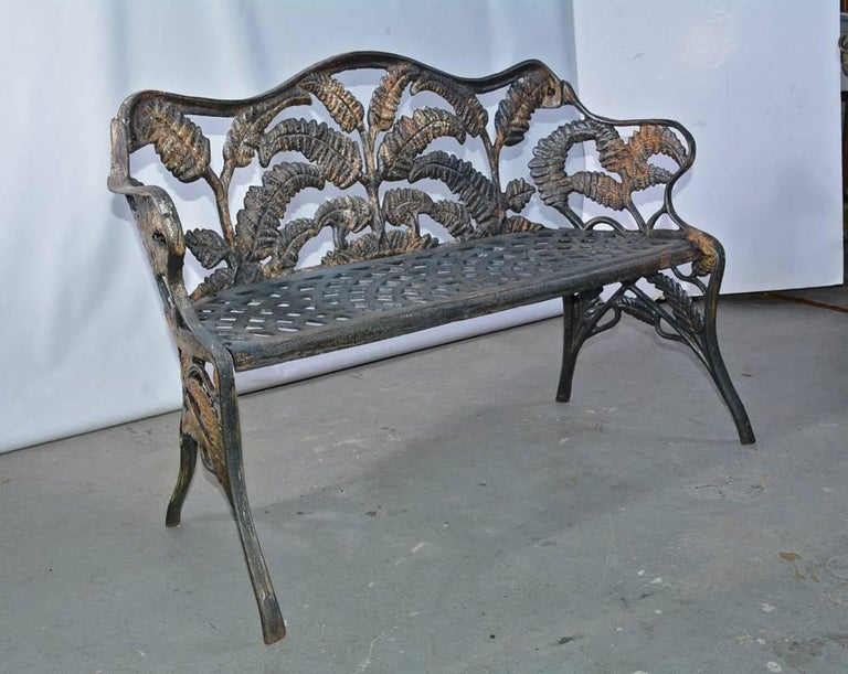 The Victorian cast-iron garden bench is decorated with sprays of ferns on the back, arms and legs. The seat has an open filigree pattern. Sections of the settee were cast separately and then screwed together. The weight is substantial.