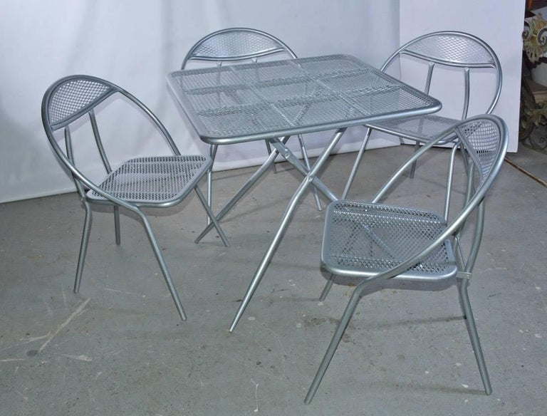 The Mid-Century Modern metal patio or garden table and matching four chair dining set, painted silver, fold flat for storage purposes. The square table has a mesh surface, while the chairs with rounded-back have mesh seats and partially mesh backs.