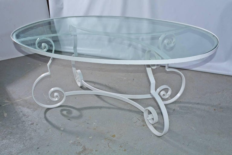The oval midcentury patio or porch dining table has an iron base and glass top. The base is designed with baroque scroll legs and curved braces that match the curved braces supporting the top. The table is painted white.