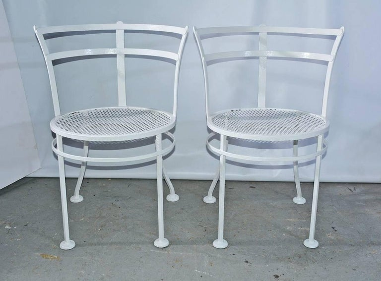 The pair of midcentury metal patio/garden chairs have rounded backs, mesh seats and a separate ring attached to the padded legs for additional sturdy support. The chairs are painted white. 