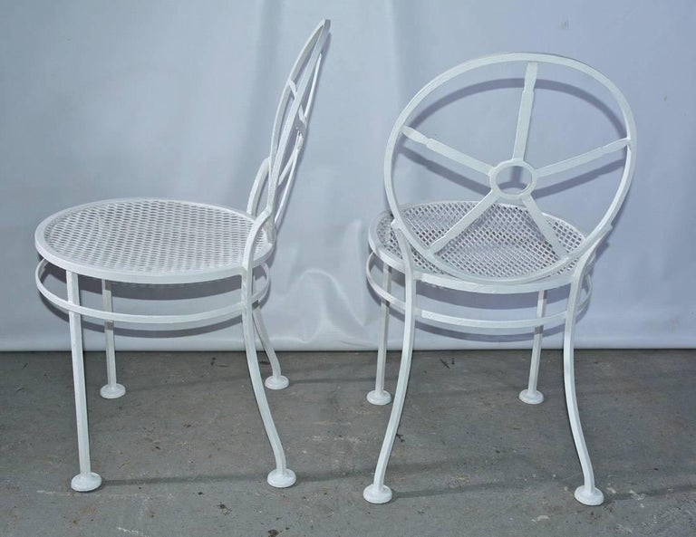 The pair of modern metal porch/garden dining chairs have circular backs divided into pie-shaped sections, mesh seats and an additional ring attached to the footed legs for sturdy support. The chairs are painted white.