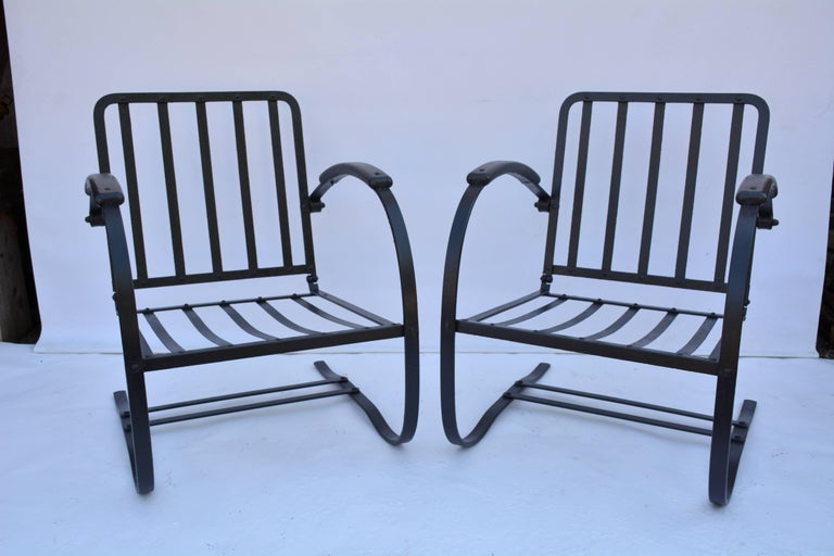 Comfortable and inviting black metal garden or porch arm chairs have a spring action for added comfort. The arms are