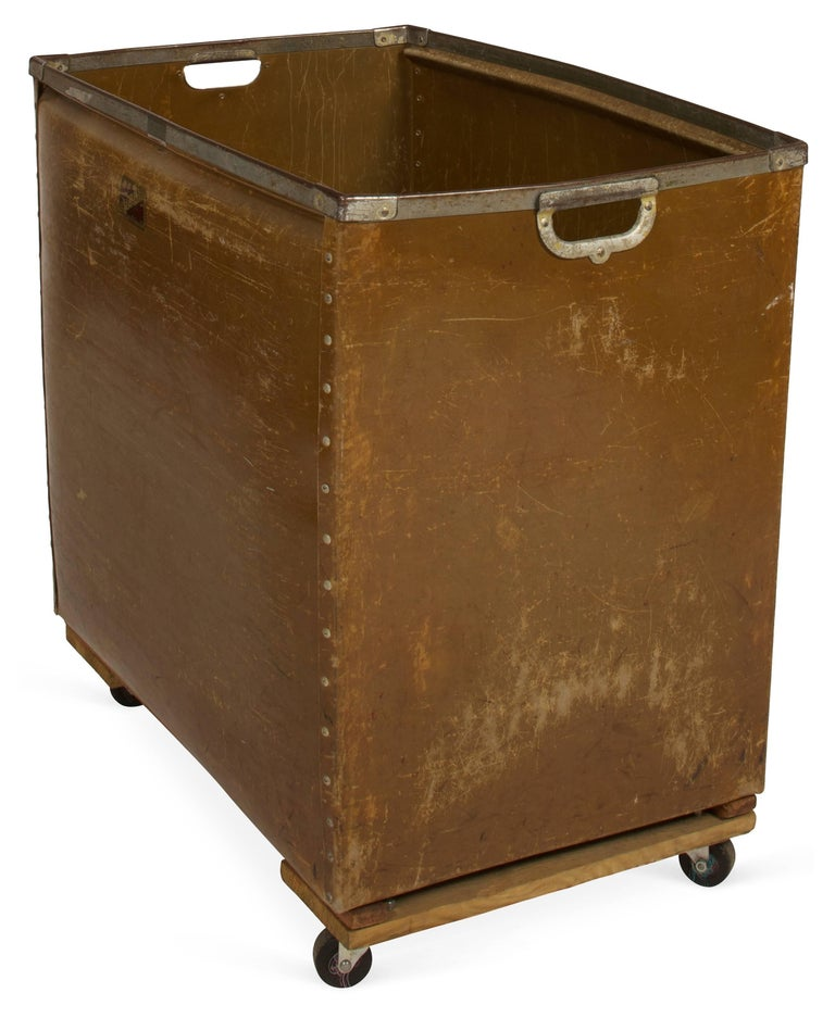 The large industrial cart is made by Kennett with two-hole handles, iron braces and metal studs on casters. These were used for moving or sorting mail. Can be wonderful as laundry basket, toy chest or storage cart. Made of thick wax coated