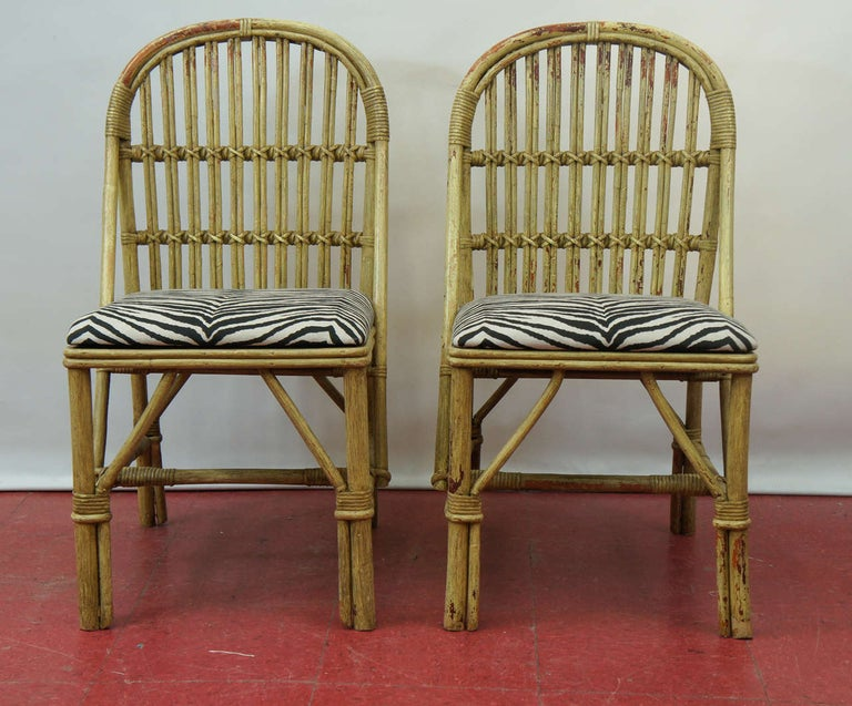 A wonderful stylish pair of painted bamboo side chairs. Seat cushions covered in cotton zebra fabric. Paint has been mostly worn off leaving wonderful patina combining the rustic and elegant feel at the same time.
