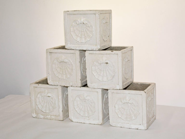 The six vintage planters are made of cast cement with white ceramic glaze decorated on all four sides with sea shells en relief. Single holes in the bottom are for drainage. Priced per piece.
