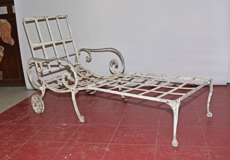 The vintage white wrought iron outdoor reclining chaise longue is moveable with its pair of wheels. The backrests on a moveable bar for flexible positioning or folds down for storage. The back and seat have criss-cross slats that will hold cushions